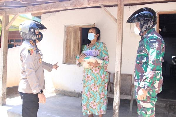 Kapolres Madiun, AKBP Jury Leonard Siahaan, memberikan daging kurban dan beras kepada seorang warga di Kabupaten Madiun, Selasa (20/7/2021). (Istimewa/Polres Madiun)